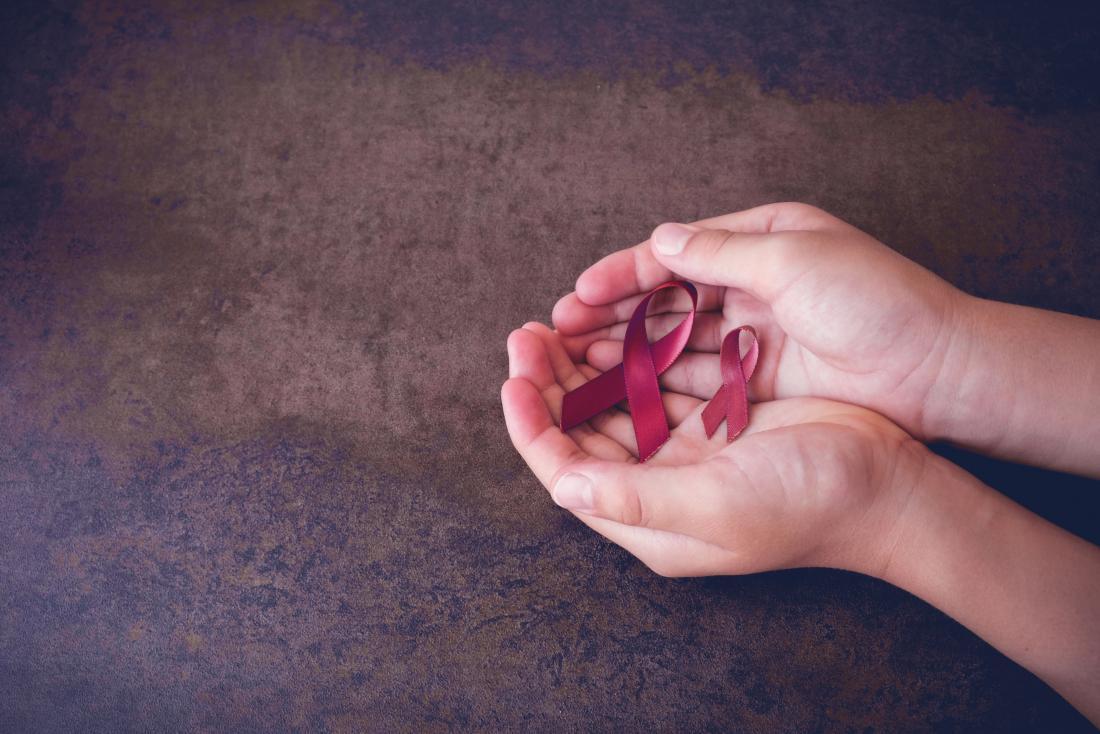 人の手で保持されている多発性骨髄腫の赤紫色のリボン。