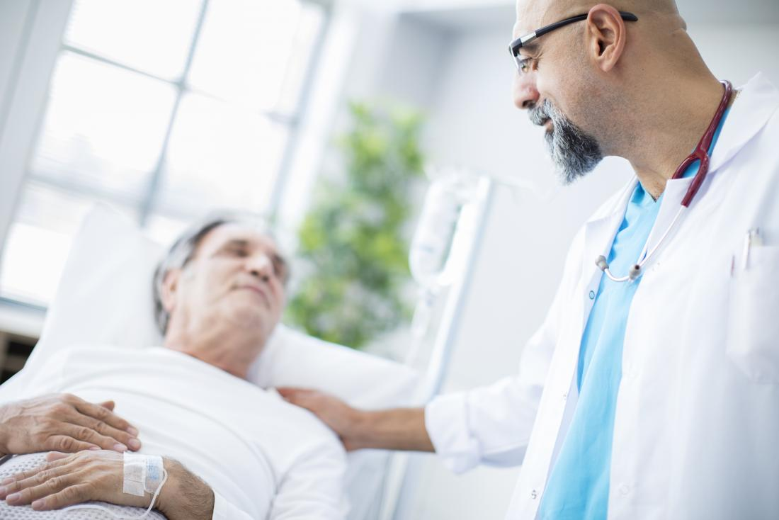 フレンドリーな医者を見上げ病院のベッドで病気の高齢者の患者。
