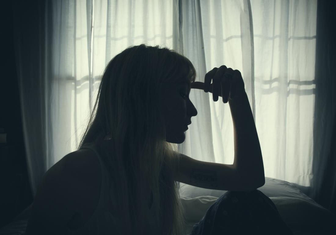 Una donna triste seduta vicino alla finestra