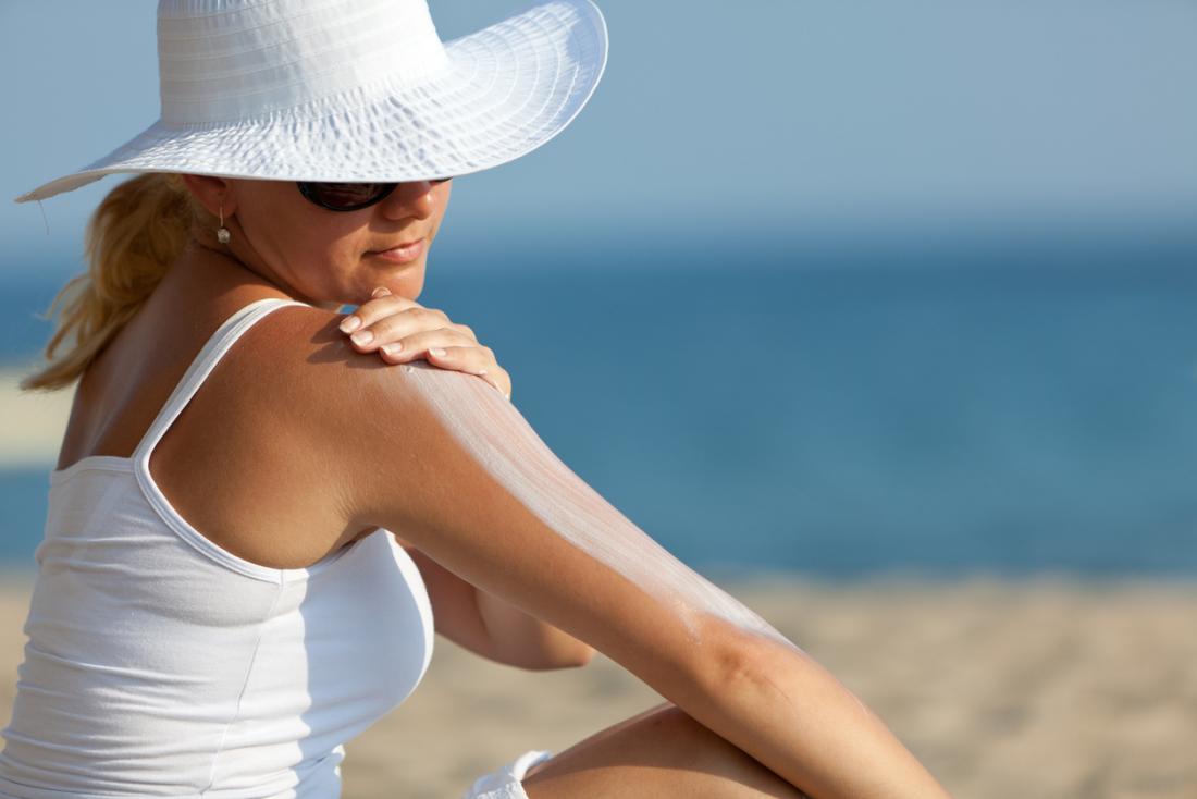 Femme appliquant une lotion solaire