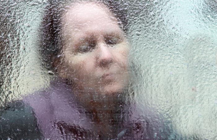 [mulher olhando através de um copo gelado]