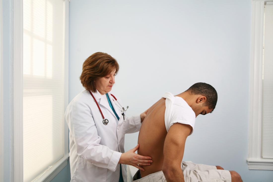 若い男性を背中の痛みで診断する医者