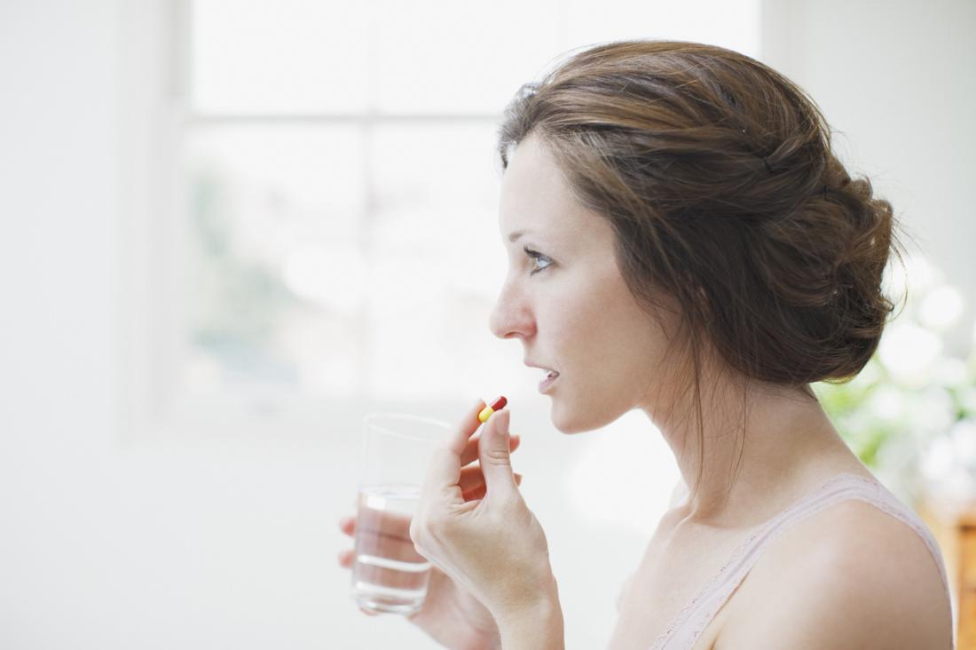 Mulher que olha no espelho ao tomar comprimidos