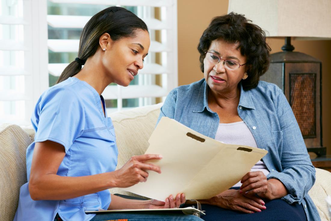 Mulher afro-americano sênior que fala com a enfermeira nova.