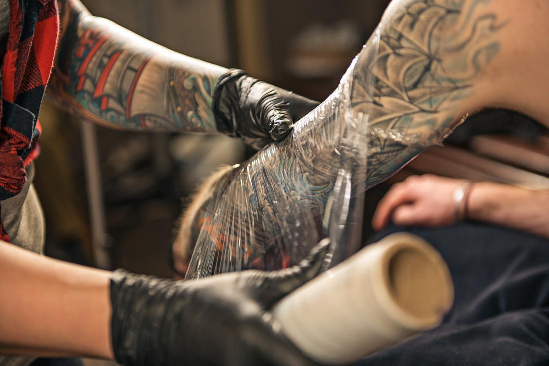 Artista del tatuaggio che avvolge il braccio del cliente in un film di plastica per incoraggiare la guarigione del tatuaggio.