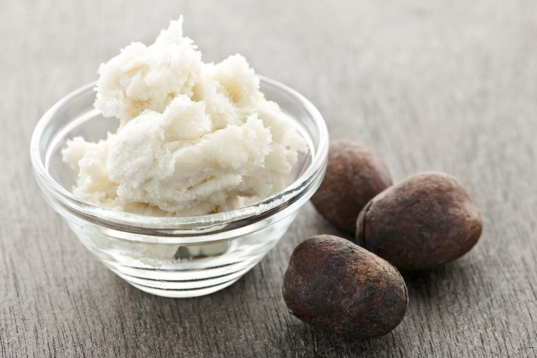 Beurre de karité dans un bol à côté des noix de karité.