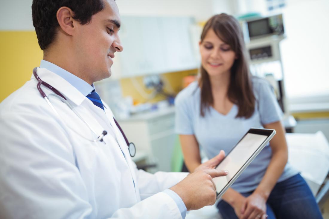 Homme médecin parlant à une jeune patiente tout en utilisant une tablette.