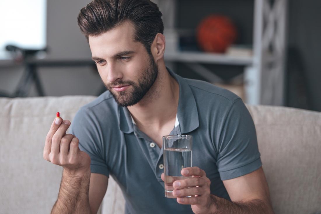 赤い丸薬と水のガラスを持っている男