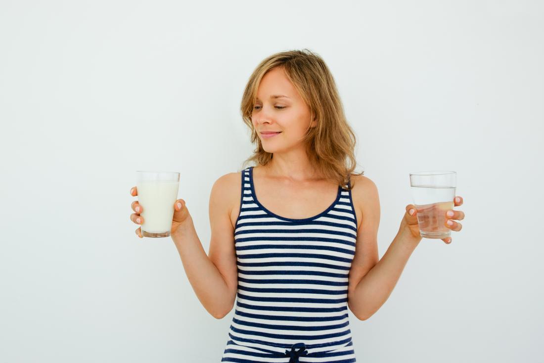 片方の手にミルクのガラスを、もう片方に水の入った若い女性