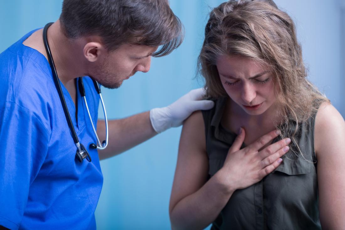 Jovem mulher mantém o peito em dor enquanto uma enfermeira ajuda
