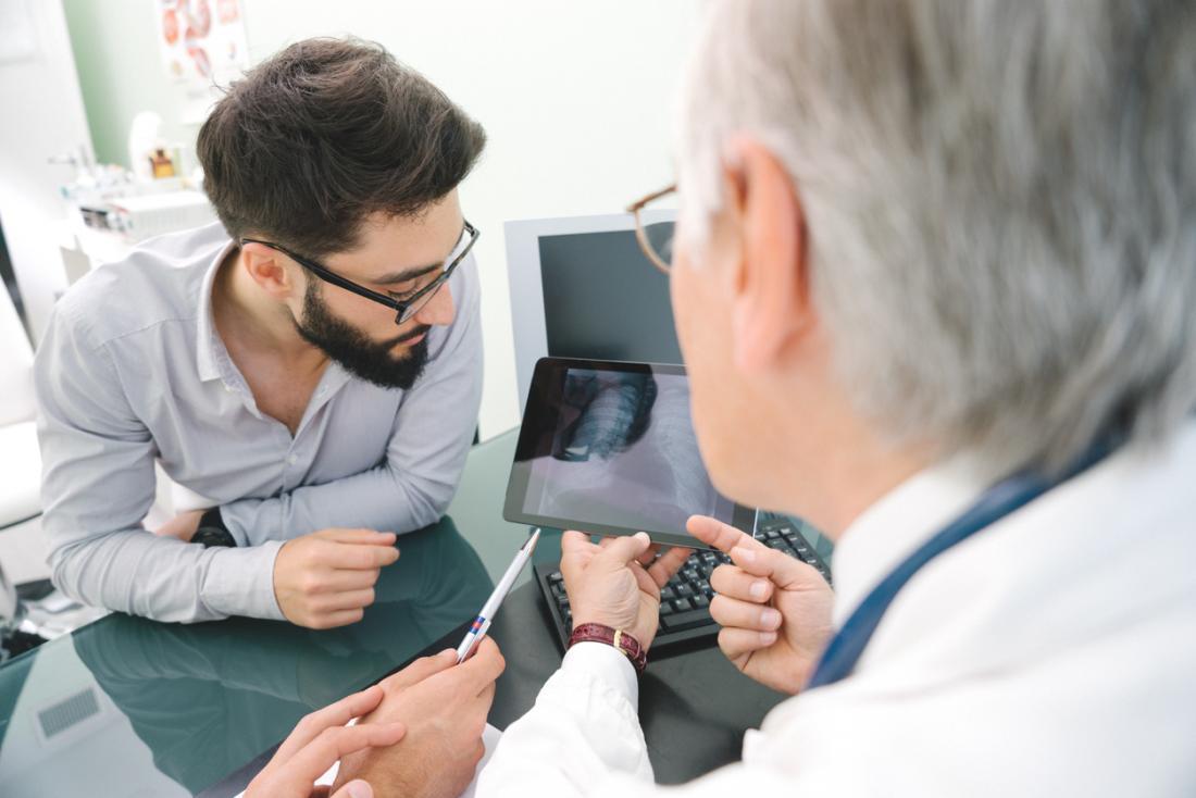 Um médico olha para um raio-x do pulmão.