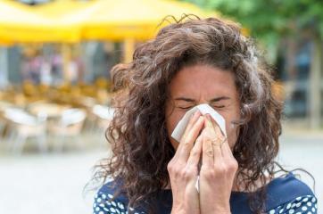 Mulher assoando o nariz.