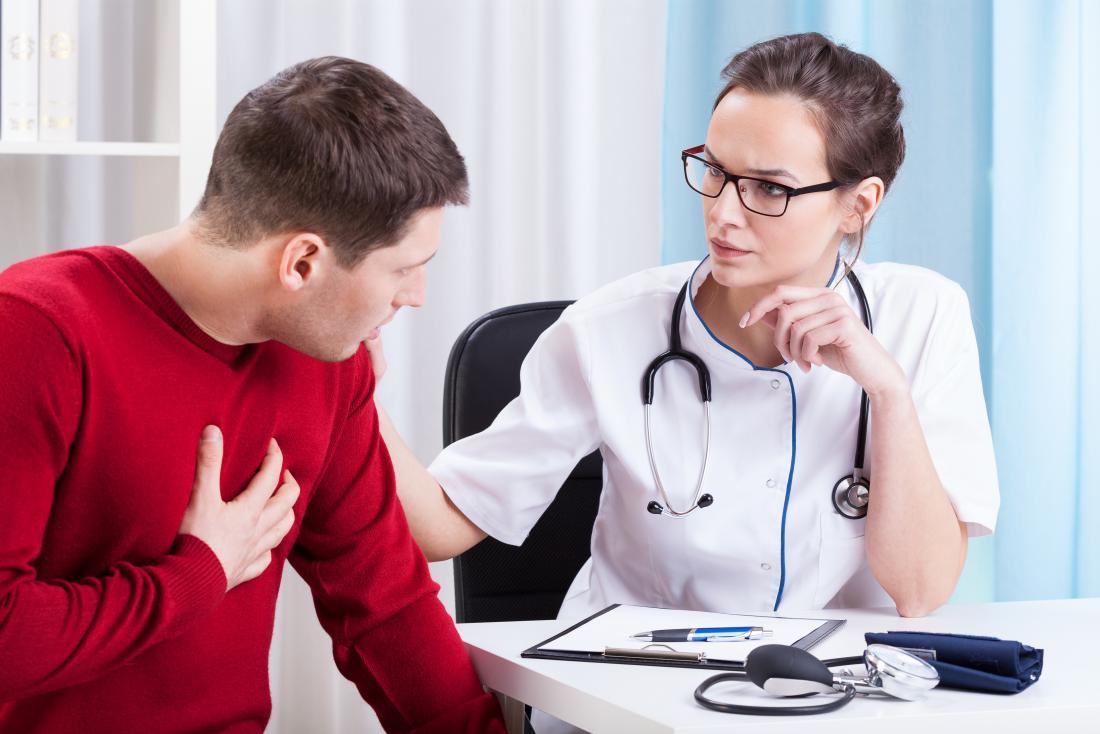 männlicher Patient, der Kasten an der Arztpraxis hält