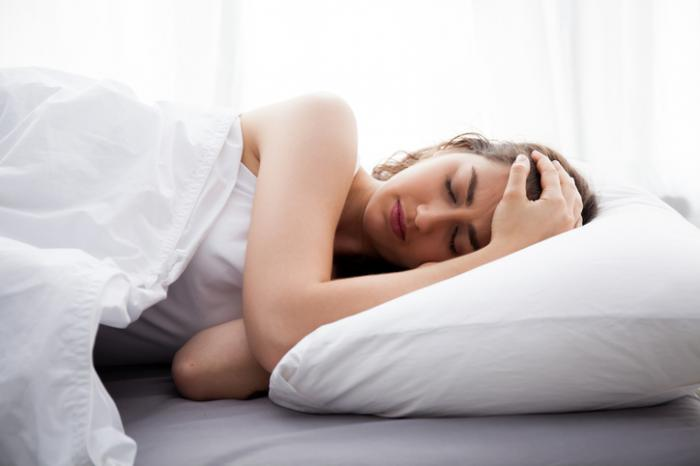 [Frau im Bett mit Migräne]