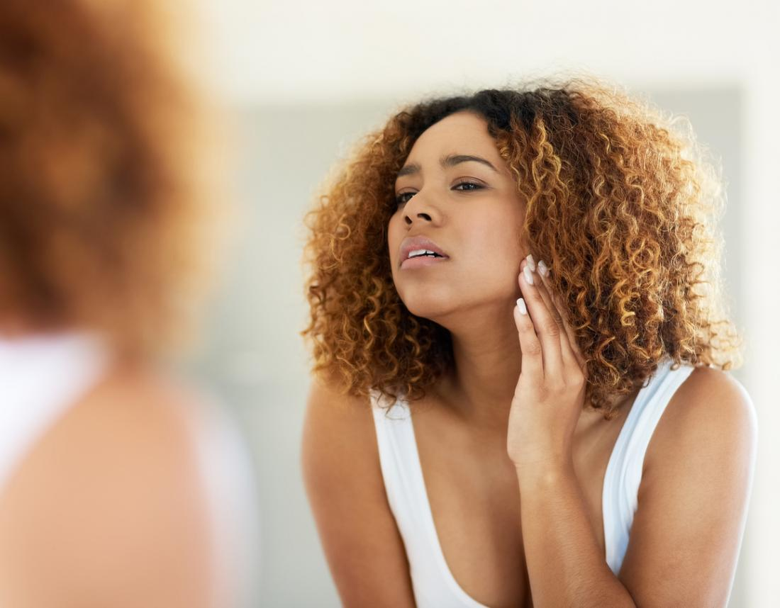 Người phụ nữ với khuôn mặt tự nhiên kiểm tra tóc trong gương.