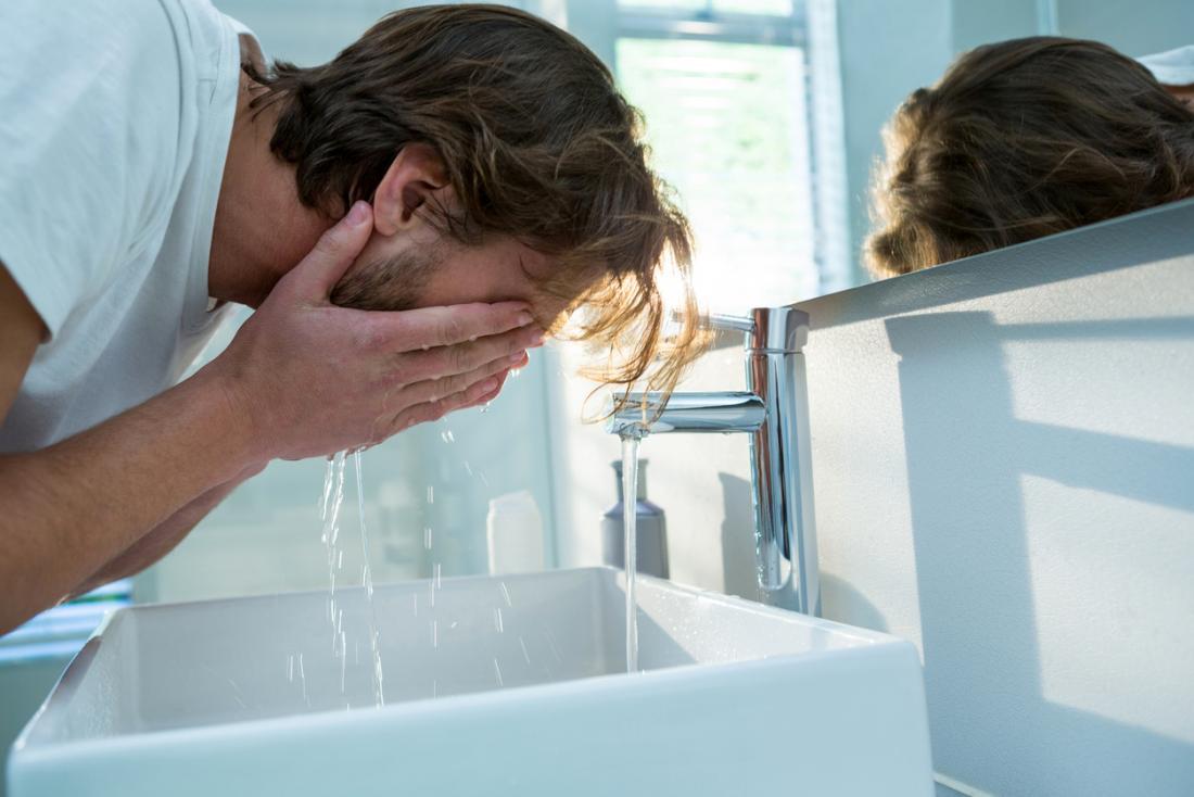 Mann, der sein Gesicht mit Wasser im Badezimmer wäscht.
