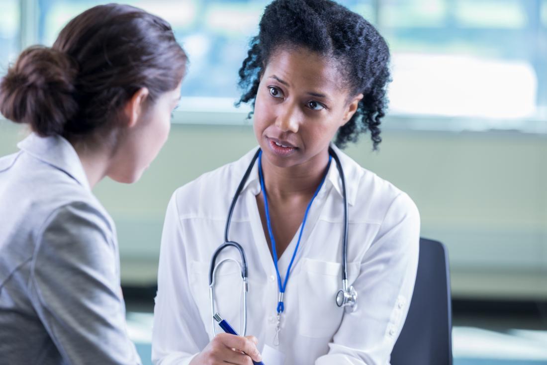 女性の病院で女性患者に話す女性の医者。
