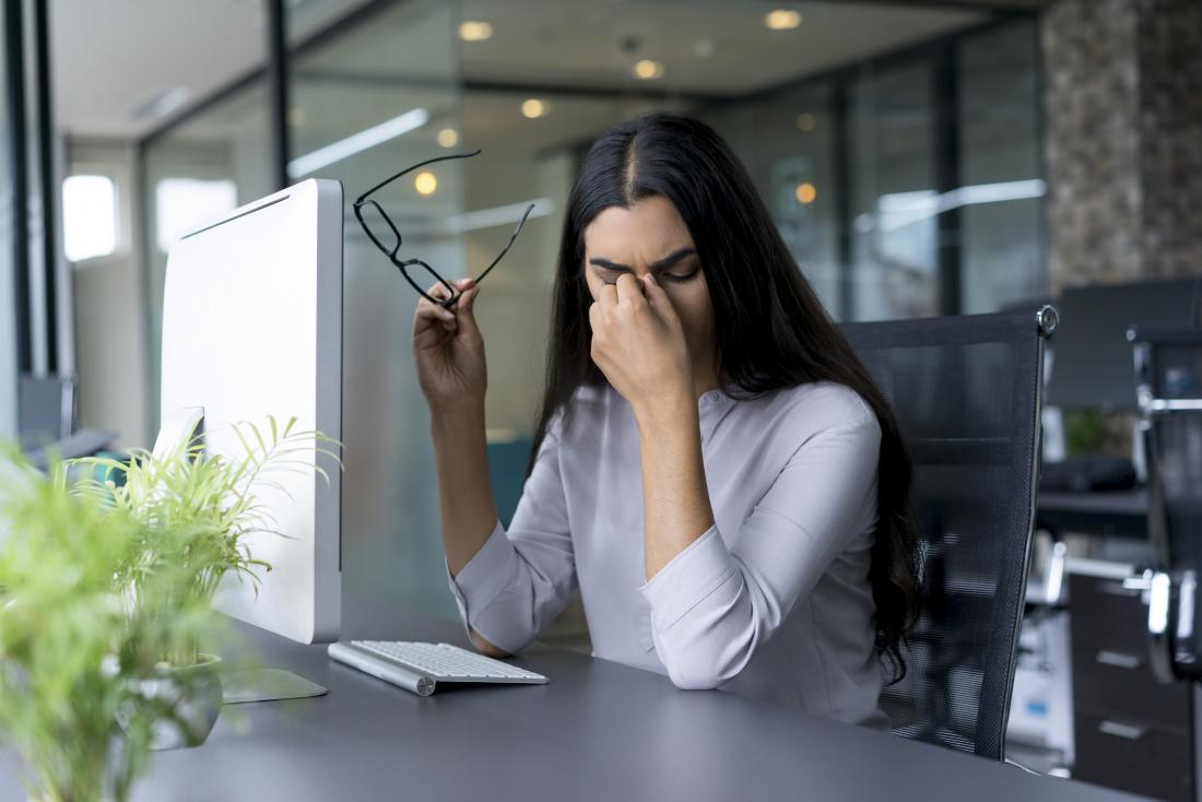 頭痛のある女性は、鼻の橋を挟んで仕事中の痛みを訴えます。