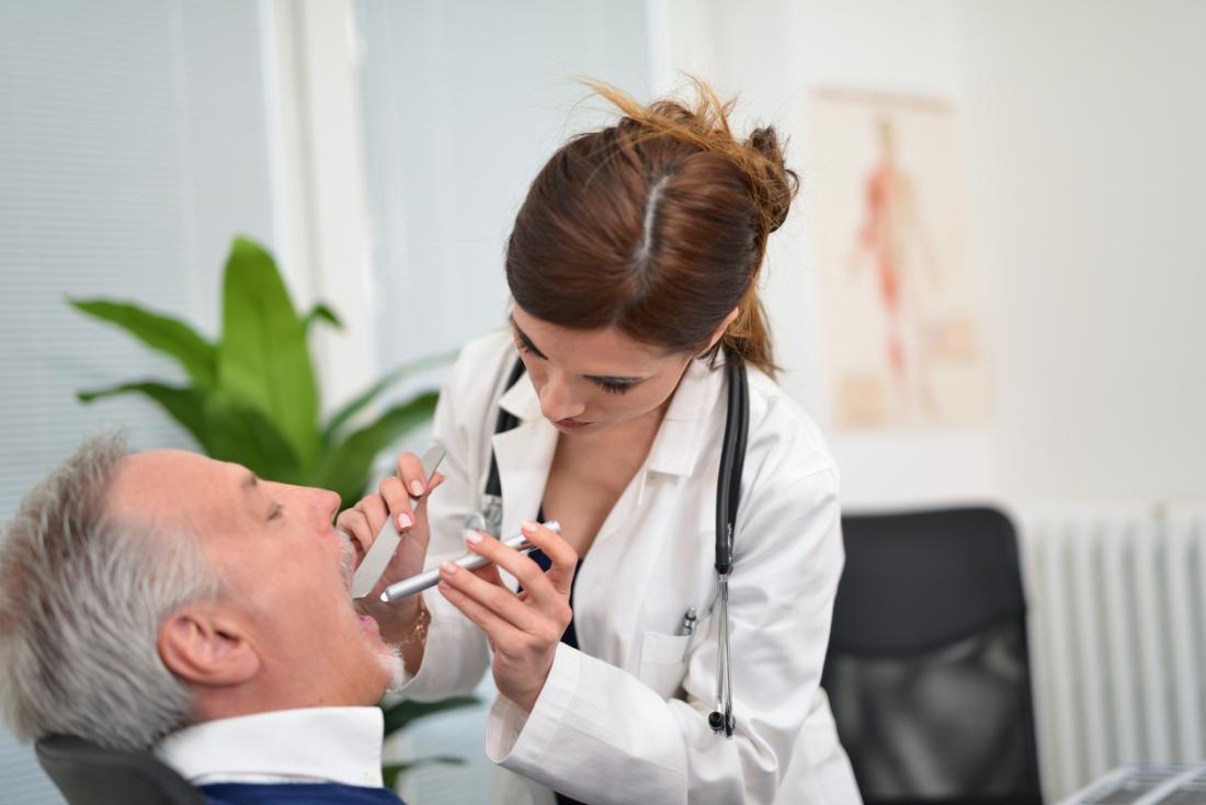 Zahnarzt, der Zähne und Mund des Patienten kontrolliert.