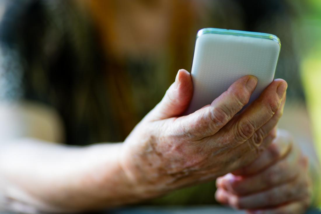 ältere Person, die Telefon hält
