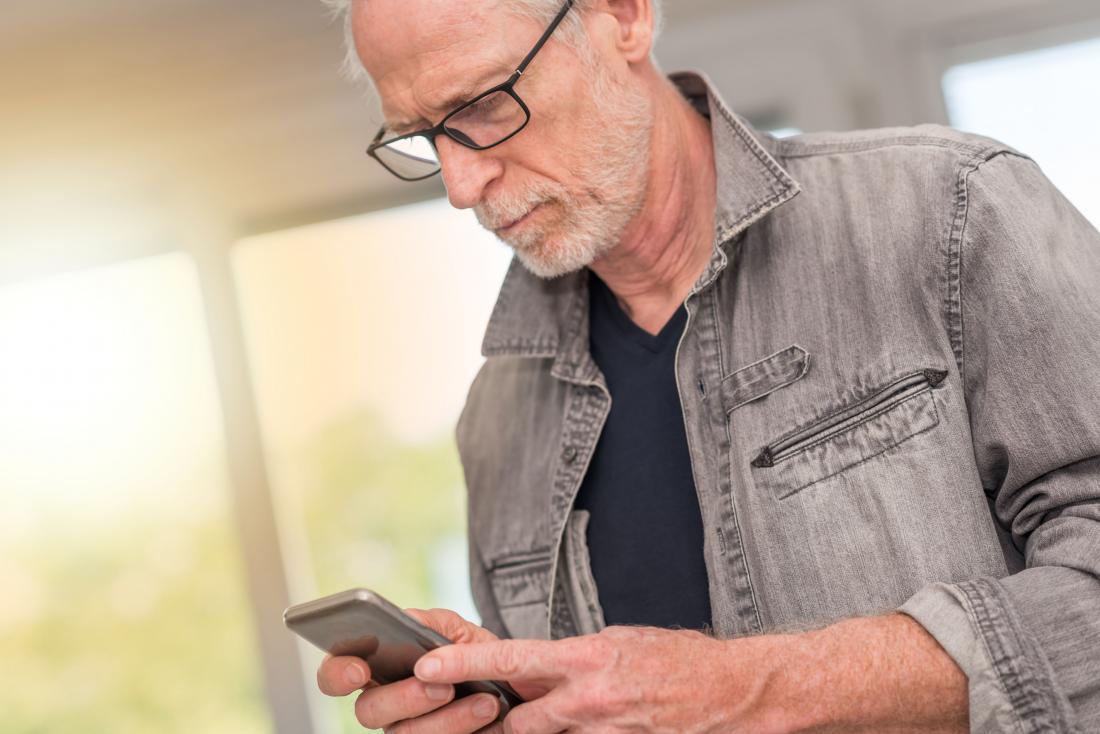 по-възрастен човек, гледащ телефона