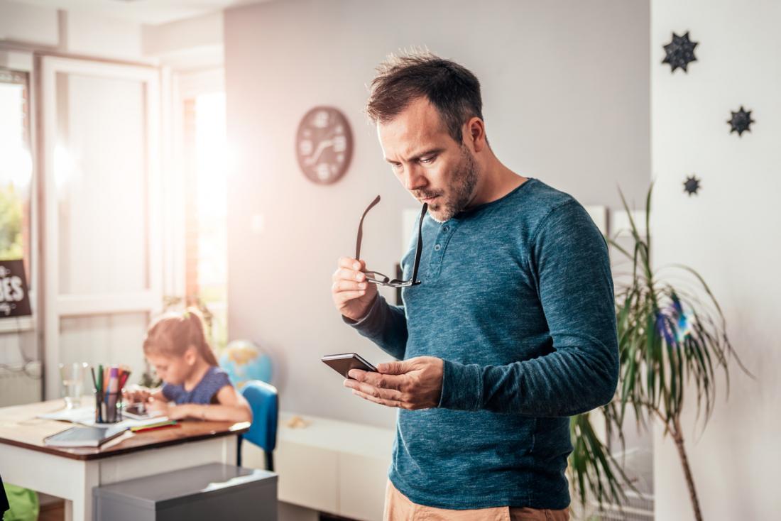 père regardant inquiet en lisant son téléphone