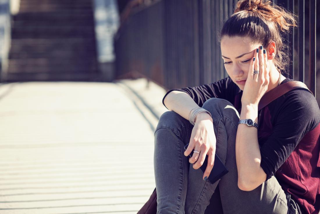 femme assise sur le sol, tenant sa tête dans la douleur et un téléphone