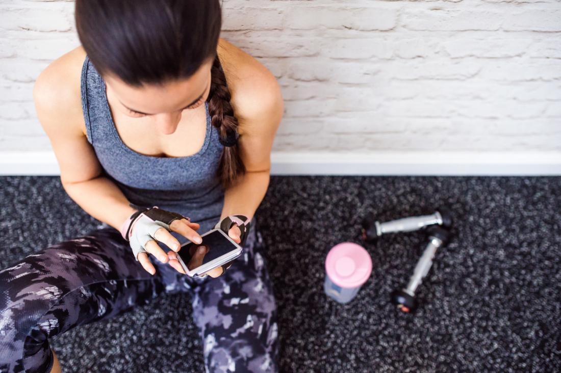 mulher segurando o telefone em uma academia