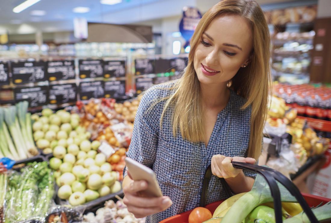 Frau, die Ernährungsinhalt des Lebensmittels auf ihrem Telefon überprüft