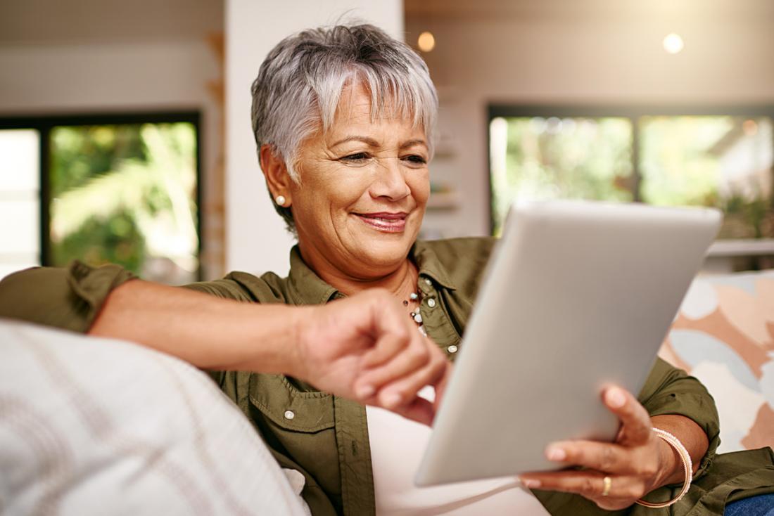 femme plus âgée regardant la tablette
