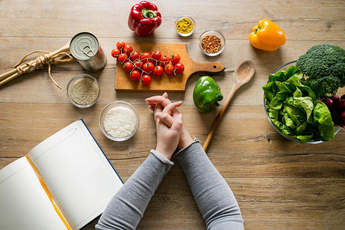 Mulher que inclina-se na tabela com vários ingredientes e um livro do planeamento da dieta.
