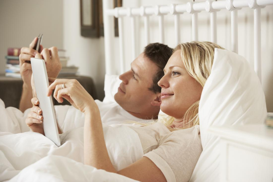 [Paar mit digitalen Tablet und Handy im Bett]