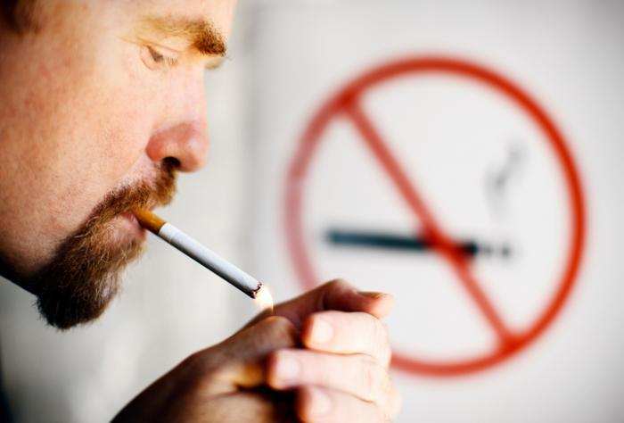 Mann, der vor Nichtraucherzeichen raucht