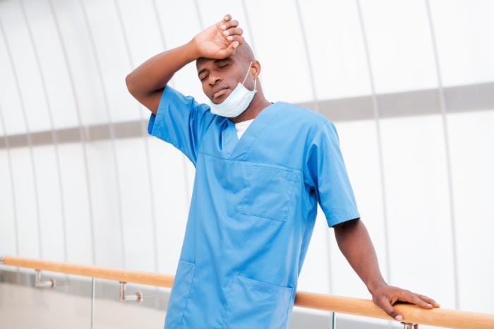 Уморен лекар с ръка на главата.