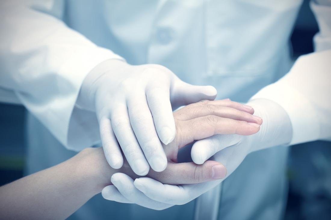 [Ein Arzt hält die Hand eines Patienten]