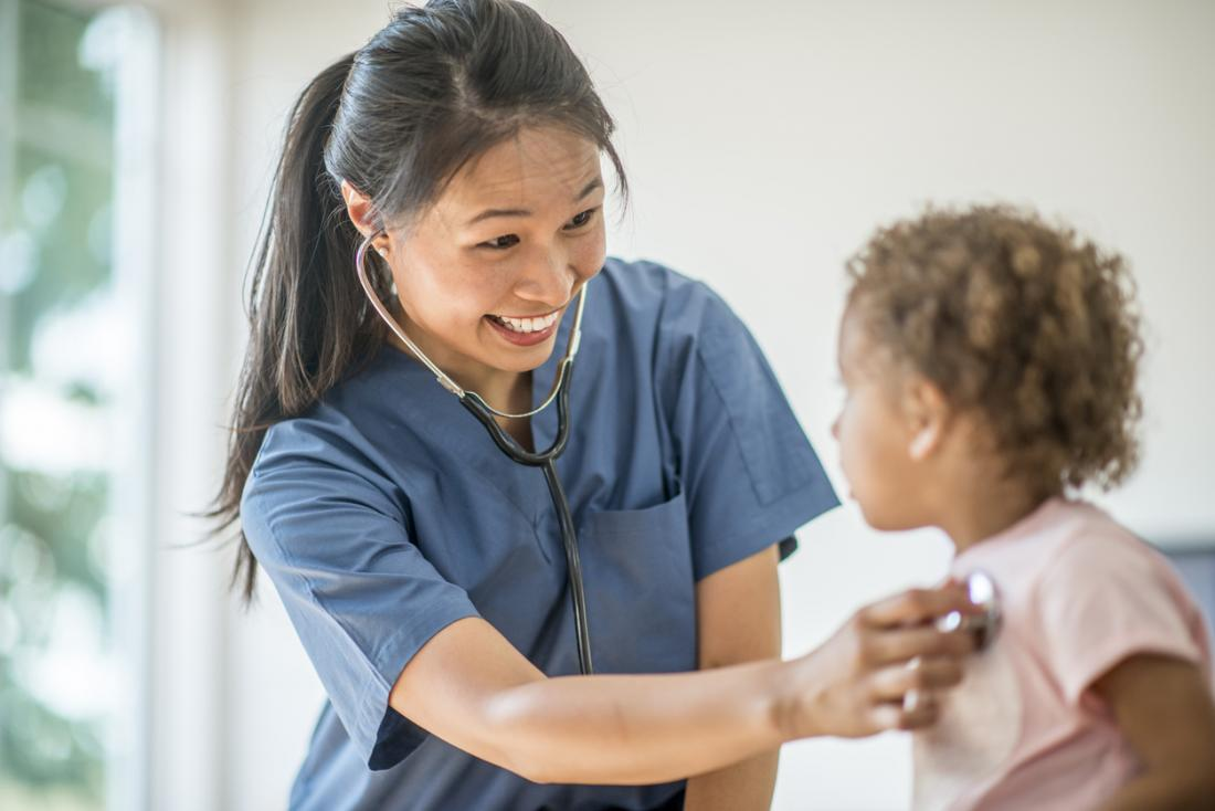 L'infirmière qui utilise un stéthoscope vérifie la respiration et le rythme cardiaque de l'enfant.