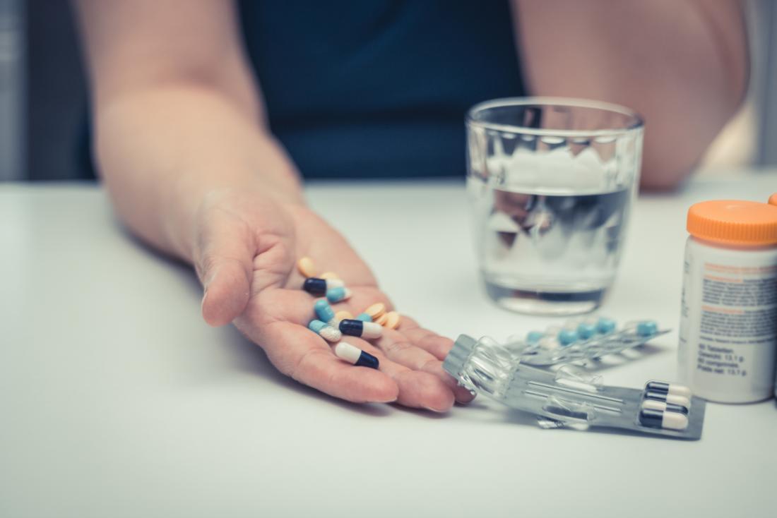 mulher olhando para pílulas