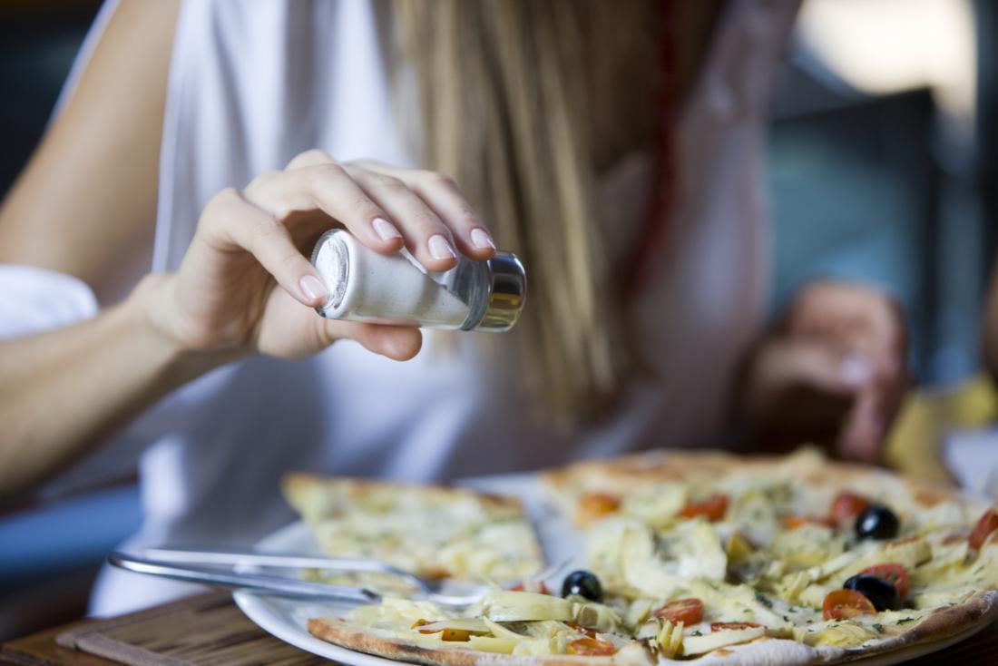 Femme saupoudrant de sel sur sa pizza.