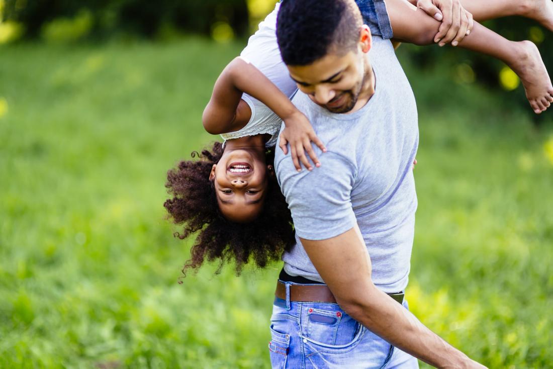 Heureux père et fille jouant à l'extérieur