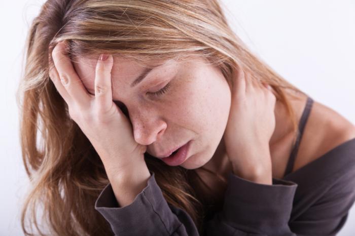 Uma mulher doente está segurando a cabeça dela.