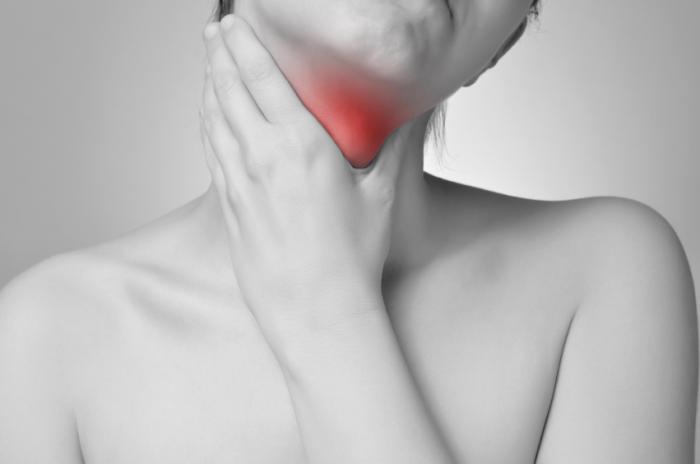 Uma mulher está segurando sua garganta vermelha brilhante.