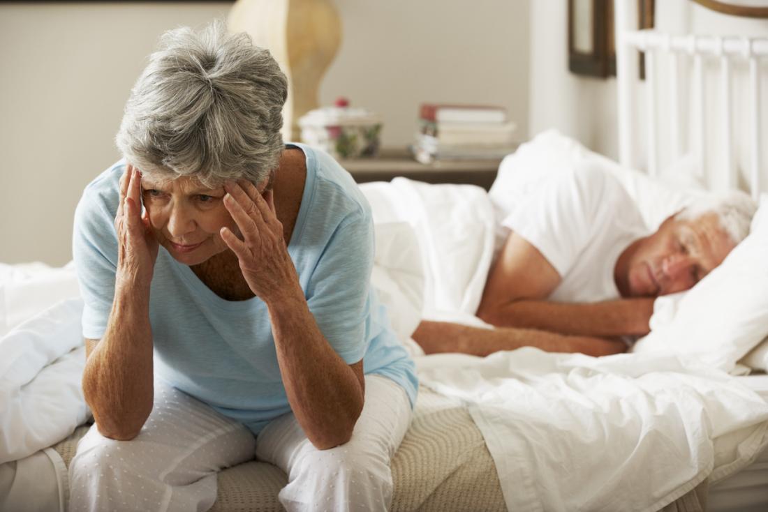 ältere Dame schaut besorgt auf ihr Bett