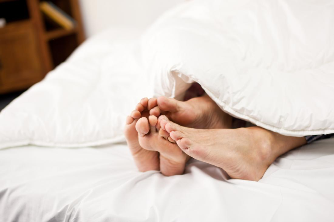 Paare Füße am Ende des Bettes