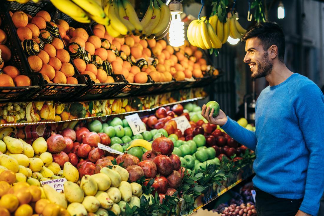 homme souriant, shopping pour les fruits
