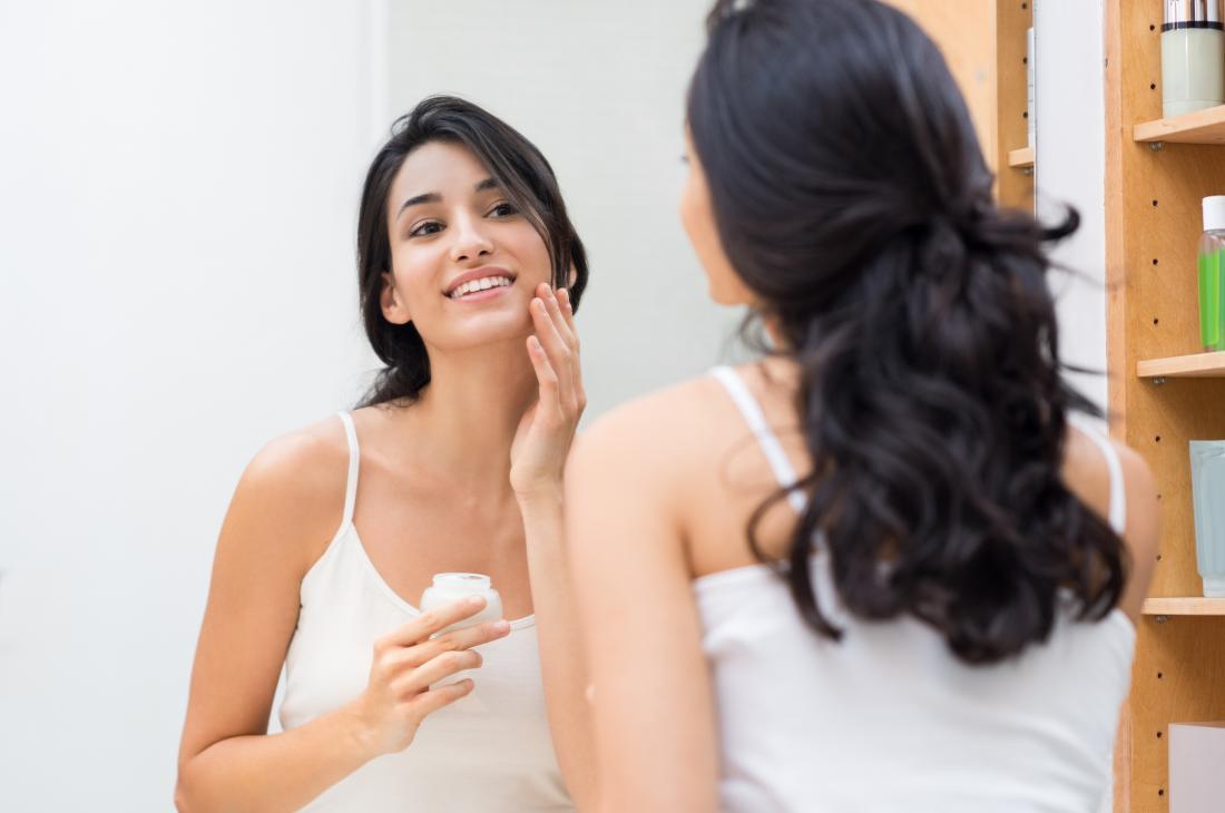người phụ nữ áp dụng kem dưỡng ẩm cho làn da dầu của mình