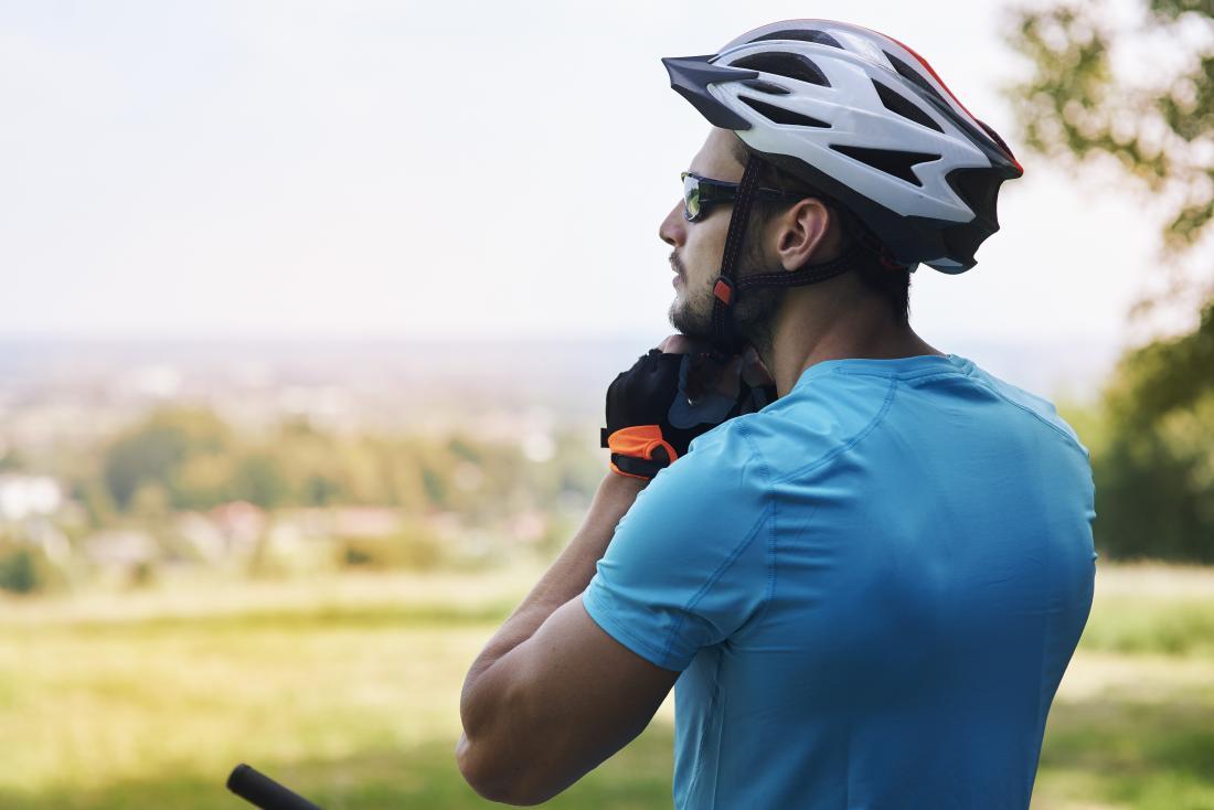 Човек, който носи каска за колоездене на открито.