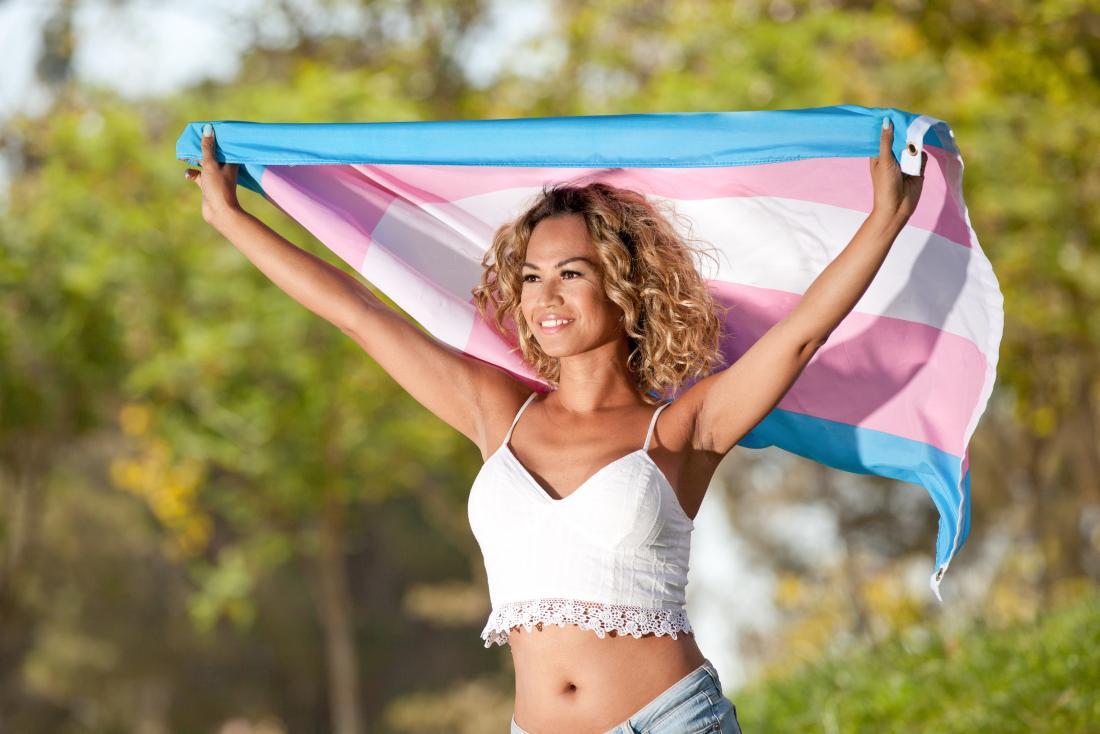 транс жена, държаща флаг