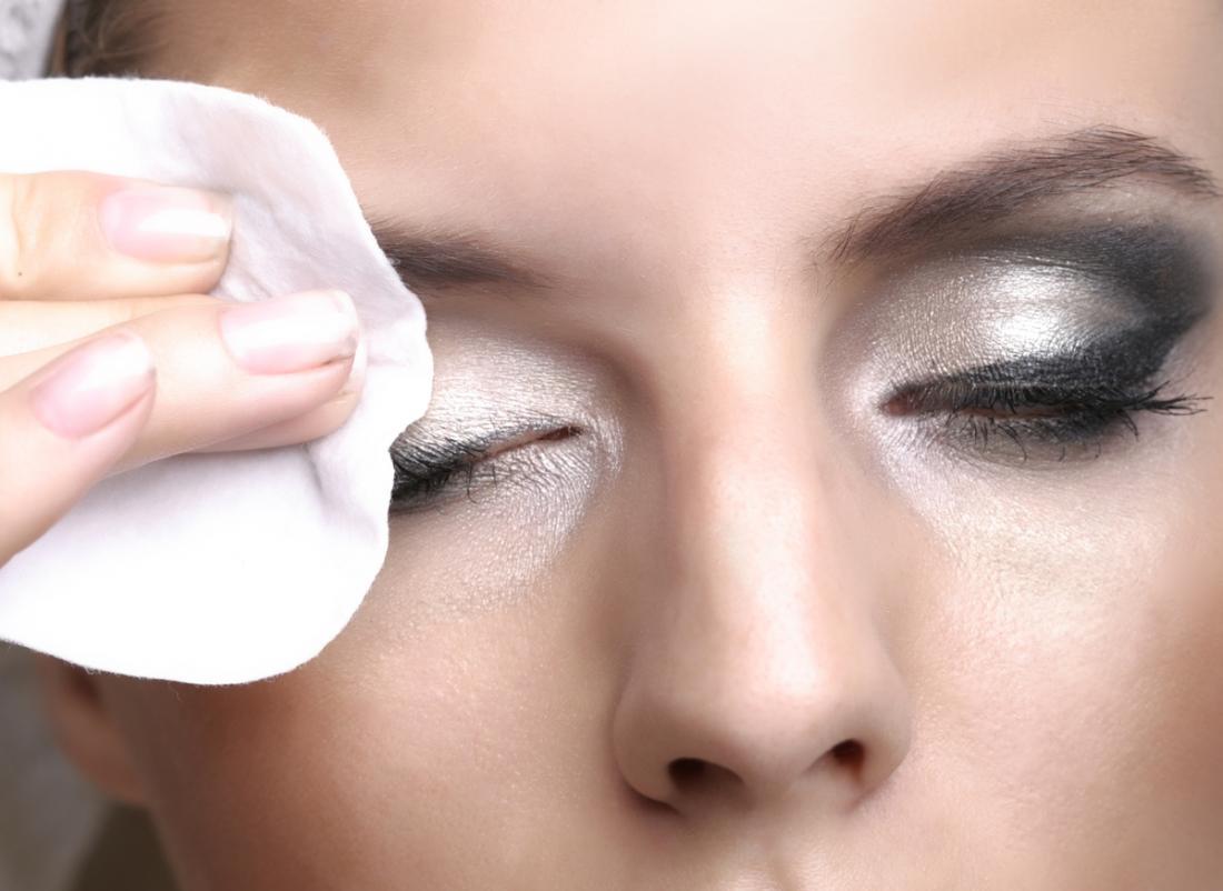 Mulher, removendo a maquiagem dos olhos.