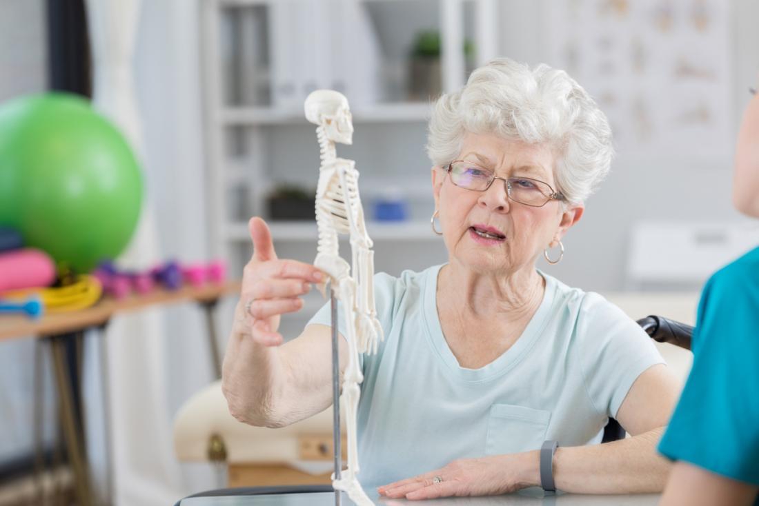 Femme âgée parlant à un ostéopathe et un chiropraticien, pointant vers un modèle de squelette pour décrire sa douleur.