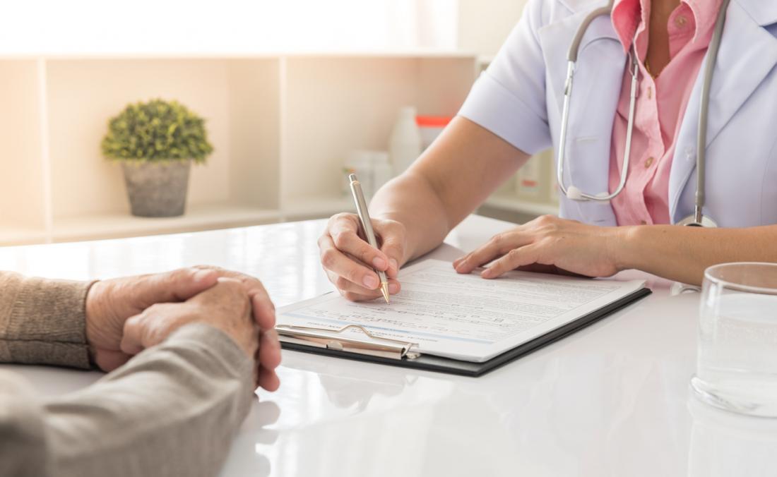 Doktor, der Anmerkungen in der Diskussion mit älterem Patienten schreibt